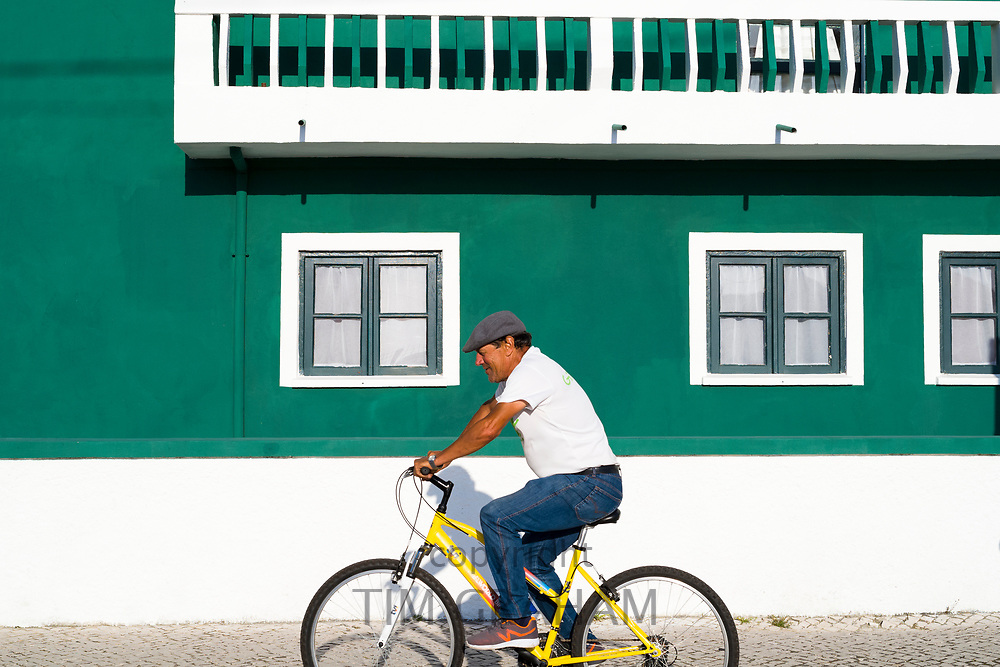 Man cycles past bright painted house in Costa Nova do Prado, a village with many holiday homes, near Aveiro,  Portugal