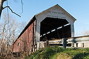 """Cox Ford Covered Bridge was built in 1913 in Burr Arch style by J.A. Britton over Sugar Creek. Turkey Run State Park, in historic Parke County, Indiana, USA. The traditional """"Cross this bridge at a walk"""" sign requires slow vehicle speed. A roof and red painted wood sides protect the historic bridge."""