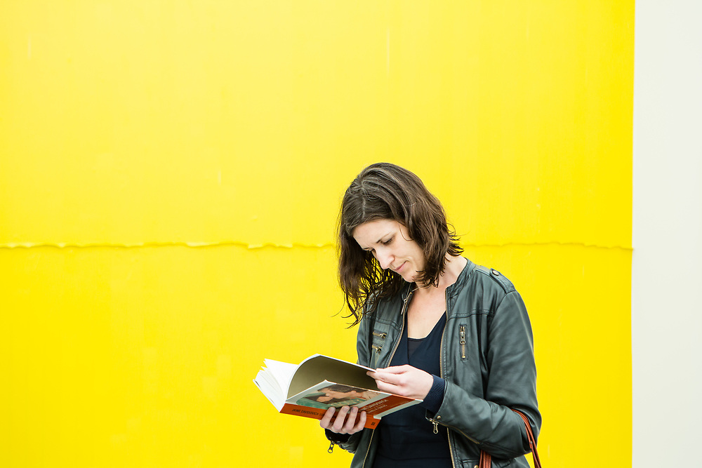New York, NY - 5 May 2017. The opening day of the Frieze Art Fair, showcasing modern and contemporary art presented by galleries from around the world, on Randall's Island in New York City. A woman reads a catalog in front of a painting by Jamie Davidovitch in the Henrique Faria gallery.