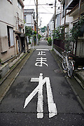 narrow residential street Japan with stop sign on pavement