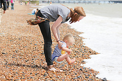 © Licensed to London News Pictures. 07/07/2014. Brighton, UK. A mother and child playing on Brighton Beach. South Coast recovers today with temperatures around 24C after a day with rain and clouds on Saturday. Photo Credit: Hugo Michiels/LNP