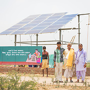 CAPTION: Bhageerat Rai, the landowner of the plot where the OORJAgram Rural Enterprise Zone is being constructed, stands proudly flanked by his son (right) and grandson (left). Behind, two construction workers display an advertising board that's designed to help passers-by visualise the opportunities this project will bring for them. LOCATION: Diara Rasulpur, Saran District, Bihar, India. INDIVIDUAL(S) PHOTOGRAPHED: From left to right - Mahendar Kumar, Manjan Kumar, Subodh Ray, Bhageerat Rai and Jeetan Rai.