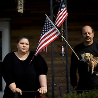 Deana Walko, 44, and George Arnott, 64, photographed on their porch with a puppy in Youngstown, OH.  Five states go to the polls today, including the winner take all Ohio, with 143 delegates for the Democrats, and 66 delegates for the Republicans.