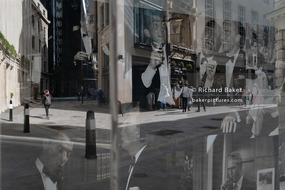 Merging with party images of the Rat Pack in the window of a menswear outfitters, are the reflection of a City workers and pedestrians in Lime Street in the City of London, the capital's financial district, on 21st August 2020, in London, England.