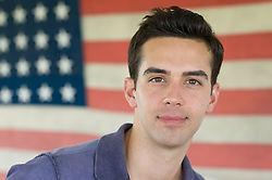 Portrait of a young man with an American flag in the background