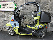 """A """"Tourist Information"""" sign in Switzerland, Europe, points towards a BMW C1 enclosed scooter, made by Bertone for BMW and sold for a limited time 2000-2001. Roll bars, safety belts, and other design features were meant to eliminate need for a helmet, which conflicted with unamended helmet laws in UK and Sweden. Other countries considered wearing a helmet with a safety belt to risk neck injuries. High center of gravity made travel at slow speeds harder to learn than for motorcycles."""
