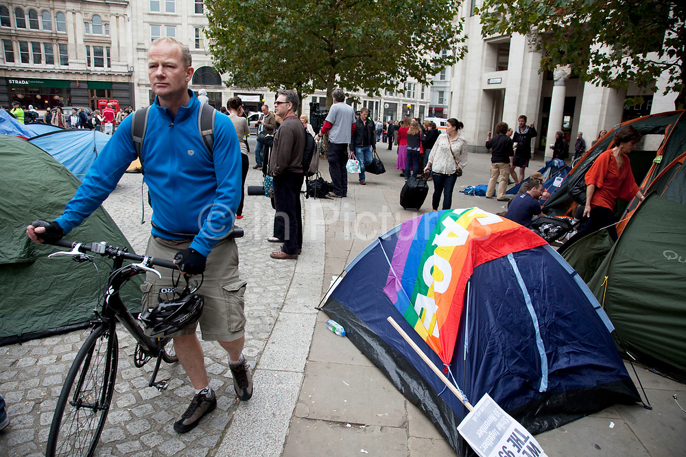 """Tents set up in the area in front of St Pauls. Occupy London protest at St Pauls, October 16th 2011. Protest spreads from the US with this demonstrations in London and other cities worldwide. The 'Occupy' movement is spreading via social media. After four weeks of focus on the Wall Street protest, the campaign against the global banking industry started in the UK this weekend, with the biggest event aiming to """"occupy"""" the London Stock Exchange. The protests have been organised on social media pages that between them have picked up more than 15,000 followers. Campaigners gathered outside  at midday before marching the short distance to Paternoster Square, home of the Stock Exchange and other banks.It is one of a series of events planned around the UK as part of a global day of action, with 800-plus protests promised so far worldwide.Paternoster Square is a private development, giving police more powers to not allow protesters or activists inside."""