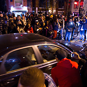 A crowd celebrating Obama's victory mobs a car with Romney stickers on U street in Washington DC after Barack Obama was announced the winner of the 2012 presidential elections.
