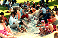 The public cool themselves in the running water of the Diana Memorial Fountain in Hyde Park, London.