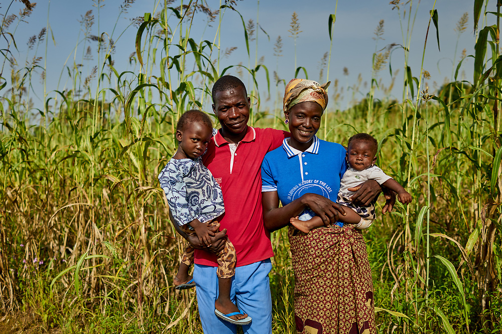 25/10/2019 Kpatua / Ghana: <br /> Felicia Ayaawin and her husband Joshua (with their youngest Luke and Ruth) pose in front of their farm. The couple are the caretakers of the Oxfam-donated solar powered pump in Kpatua.<br /> <br /> Oxfam built a solar powered pump in Kpatua to help over families become more resilient during dry seasons. Apart from community members coming to the pump twice a day, all year round, during the dry season, women use the water from the pump to farm vegetables for sale.