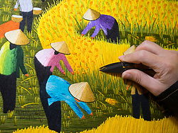 Asia, Vietnam, Ba Dinh, hand embroidering textile with framers in rice paddy