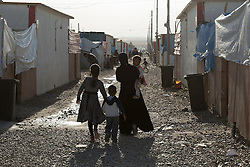 Licensed to London News Pictures. 22/10/2016. A refugee mother and her children make their way through an alley way in the Dibaga refugee camp near Makhmur, Iraq.<br />