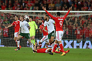 Joe Allen of Wales hits the floor dazed after taking a knock from James McClean (11) and David Meyler (18) of Republic of Ireland, the incident leads to Allen leaving injured. Wales v Rep of Ireland , FIFA World Cup qualifier , European group D match at the Cardiff city