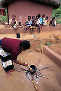 A Vendan woman stirs a pot of grasshoppers that the kids have just collected. She cooks the de-winged grasshoppers in oil and they are eaten with cornmeal porridge. Masetoni, Mpumalanga, South Africa. (Man Eating Bugs page 137B)