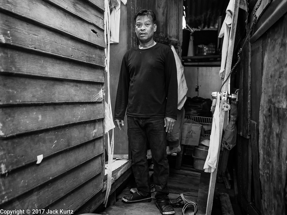 04 JULY 2017 - BANGKOK, THAILAND:  A man who has lived in Pom Mahakan his entire life in front of his new home. His family was able to prove their familial roots in the community and the city allowed them to remain. The final evictions of the remaining families in Pom Mahakan, a slum community in a 19th century fort in Bangkok, have started. An ad hoc group of housing advocates, historic preservationists and academics have asked the city to allow the remaining residents to stay and city officials have said they might allow people who can prove that their families have lived in the fort since before the 1950s, when the city got title to the land from the Thai military, will be able to stay.   PHOTO BY JACK KURTZ