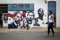 """© Licensed to London News Pictures. 14/07/2021. LONDON, UK.  A woman passes a mural by urban street artists MurWalls and commissioned by Sadiq Khan, Mayor of London, which has been unveiled in Vinegar Yard near London Bridge. Featuring the slogan """"You did us proud"""", the artwork celebrates the Engalnd football team's achievement in reaching the final of Euro 2020 and features an image of manager Gareth Southgate, captain Harry Kane and forward Raheem Sterling.  Photo credit: Stephen Chung/LNP"""