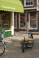 A  custom delivery bike with wheels of Beemster cheese stands in front of a delicatessen in Amsterdam.