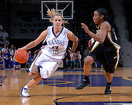 Kansas State guard Claire Coggins (14) drives to the basket against pressure from Missouri guard Tiffany Brooks (R) during the second half at Bramlage Coliseum in Manhattan, Kansas, January 13, 2007.  K-State beat the Missouri Tigers 81-66.