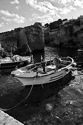Porto nella Marina di Novaglie. Si notano le barche dei pescatori, di colore prevalentemente bianco e blu, parcheggiate. Il porto è scavato nella scogliera come capita di trovare in molte marine salentine.