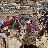 Local Sherpas bargain with lowland people who have carried big loads for several days to the weekly Saturday market in Namche Bazaar, the leading Sherpa town of Nepal's Himalaya. Although most Sherpas are Tibetan Buddhists and most lowlander are Hindu, this is not a source of conflict.