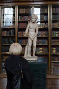 A visitor admires a sculpture of Cupid, a 2nd century Roman copy of a Greek original, in the Enlightenment Gallery of the British Museum, on 11th April 2018, in London, England.