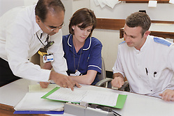 Doctor talking to deputy sister and staff nurse at workstation on spinal unit of hospital,