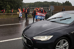 Colnbrook, UK. 27th September, 2021. Insulate Britain climate activists arrive to block a slip road from the M25 at Junction 14 close to Heathrow airport as part of a campaign intended to push the UK government to make significant legislative change to start lowering emissions. The activists are demanding that the government immediately promises both to fully fund and ensure the insulation of all social housing in Britain by 2025 and to produce within four months a legally binding national plan to fully fund and ensure the full low-energy and low-carbon whole-house retrofit, with no externalised costs, of all homes in Britain by 2030.