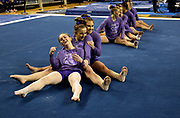 Lauren Farley, Abby Heiskell, and Maddie Mariani of the Michigan Wolverines smile after competing in their Flip for Chip meet against Nebraska at the Crisler Center on February 3, 2019 in Ann Arbor, Michigan.