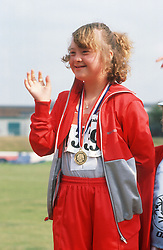 Young woman with disability standing on podium at Special Olympics wearing medal around neck waving and smiling,