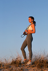 Woman with a jump rope standing on a sand dune at sunset