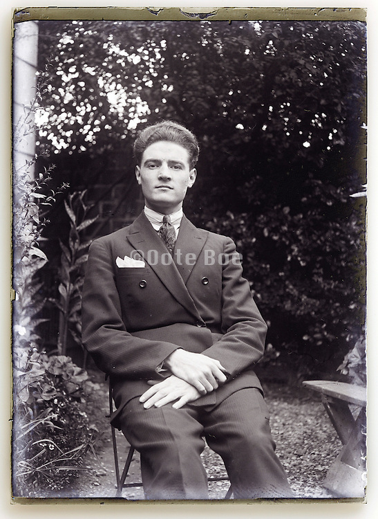 well dressed young adult man sitting in garden setting 1930s