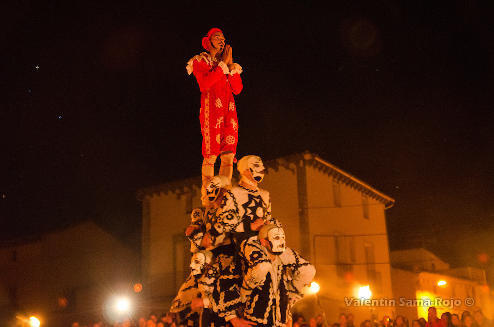 The 'contradancero' impersonating the devil at the top of an human tower acting as he prays.