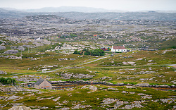 View of on solitary cottage amongst rocky barren landscape on The Bays on East coast of Isle of Harris, Outer Hebrides, Scotland, UK