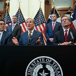 Texas Gov. Greg Abbott poses after signing two bills strengthening the Texas power grid and infrastructure that were emergency items on his legislative agenda. The bills were in response to February's winter storm that nearly knocked out the Texas power grid.  At left is Rep. Chris Paddie, R-Marshall, at right, Sen. Kelly Hancock, R-North Richland Hills.