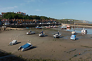 Boats at low tide in Folkestone, England, United Kingdom. Folkestone is a port town on the English Channel, in Kent, south-east England. The town lies on the southern edge of the North Downs and was an important harbour and shipping port for most of the 19th and 20th centuries.