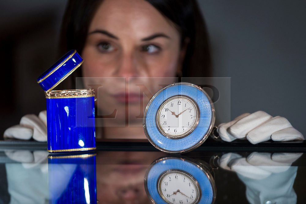"""© Licensed to London News Pictures. 19/03/2021. LONDON, UK. A staff member views a """"Fabergé Imperial two-colour gold-mounted guilloché enamel cigarette case, workmaster Michael Perchin, St Petersburg, 1899-1903"""", (est. £8,000-12,000) and a """"Fabergé Imperial gold and silver-gilt mounted guilloché enamel timepiece, workmaster Michael Perchin, St Petersburg, 1899-1903"""", (est. £15,000-25,000).  Preview of the upcoming sale of property from the collection of the Patricia Knatchbull, 2nd Countess Mountbatten of Burma.  Over 350 lots spanning jewellery, furniture, paintings, sculpture, books, silver, ceramics & objets d'art are to be auctioned on 24 March at Sotheby's New Bond Street galleries.  Photo credit: Stephen Chung/LNP"""