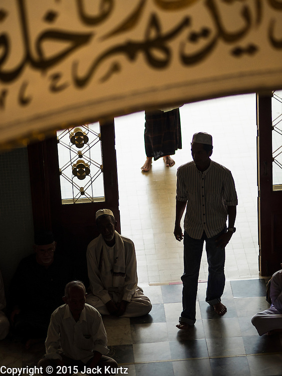 19 JUNE 2015 - PATTANI, PATTANI, THAILAND: A man walks into Pattani Central Mosque before Friday midday prayers.  Pattani Central Mosque is the main mosque in Pattani and was built in 1963. It is especially crowded during Ramadan, when the crowd frequently spills out into the street.     PHOTO BY JACK KURTZ