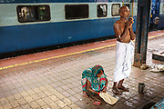 Before boarding their train, a man offers a silent prayer whilst his wife gathers their belongings