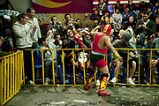 Male wrestler flying into crowd of foreign travellers. Lucha Libre wrestling origniated in Mexico, but is popular in other latin Amercian countries, including in La Paz / El Alto, Bolivia. Male and female fighters participate in the theatrical staged fights to an adoring crowd of locals and foreigners alike.