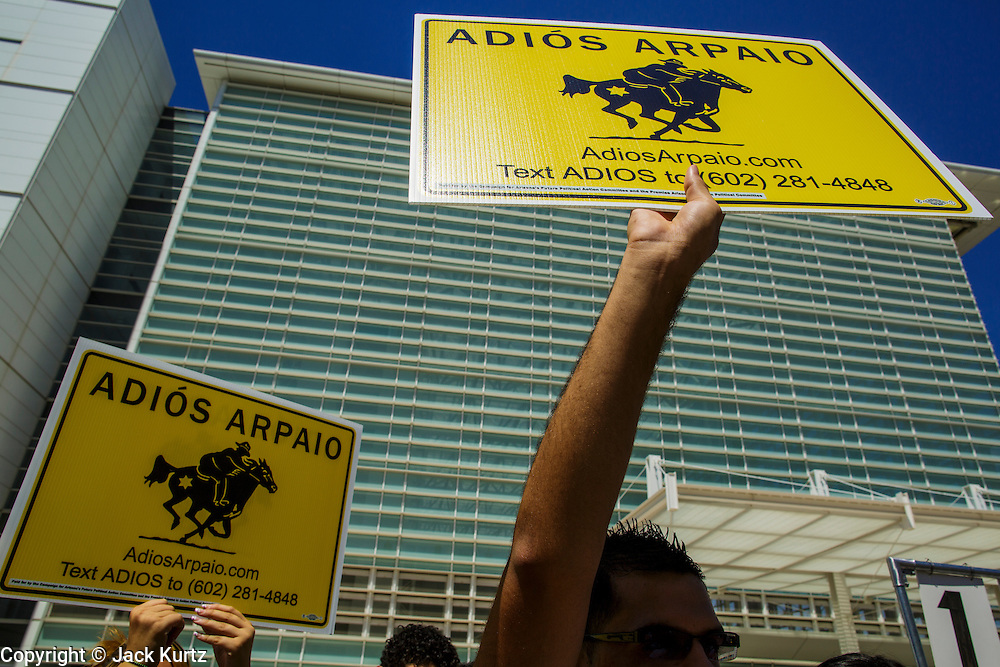 01 AUGUST 2012 - PHOENIX, AZ:  People hold up signs in front of the US Courthouse in Phoenix Wednesday. About 200 people, mostly Latino immigrants' rights and civil rights activists, gathered in front of the Sandra Day O'Connor Courthouse in Phoenix Wednesday to pray on what is expected to be the last day of testimony in the racial profiling trial against Maricopa County Sheriff Joe Arpaio. The suit, brought by the ACLU and MALDEF in federal court against Maricopa County Sheriff Joe Arpaio, alleges a wide spread pattern of racial profiling during Arpaio's ''crime suppression sweeps'' that targeted undocumented immigrants. U.S. District Judge Murray Snow granted the case class action status opening it up to all Latinos stopped by Maricopa County Sheriff's Office deputies during the crime sweeps. The case is being heard in Judge Snow's court.    PHOTO BY JACK KURTZ