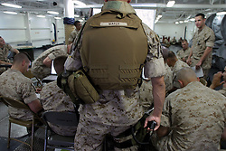 A hand on his side arm, Lt. Colonel John L. Mayer - commanding officer of the 1st Battalion, 4th Marines, 1st Marine Division - listens as junior officers  wargame through possible situations the MEU's troops will face in their area of operations in Iraq.<br />