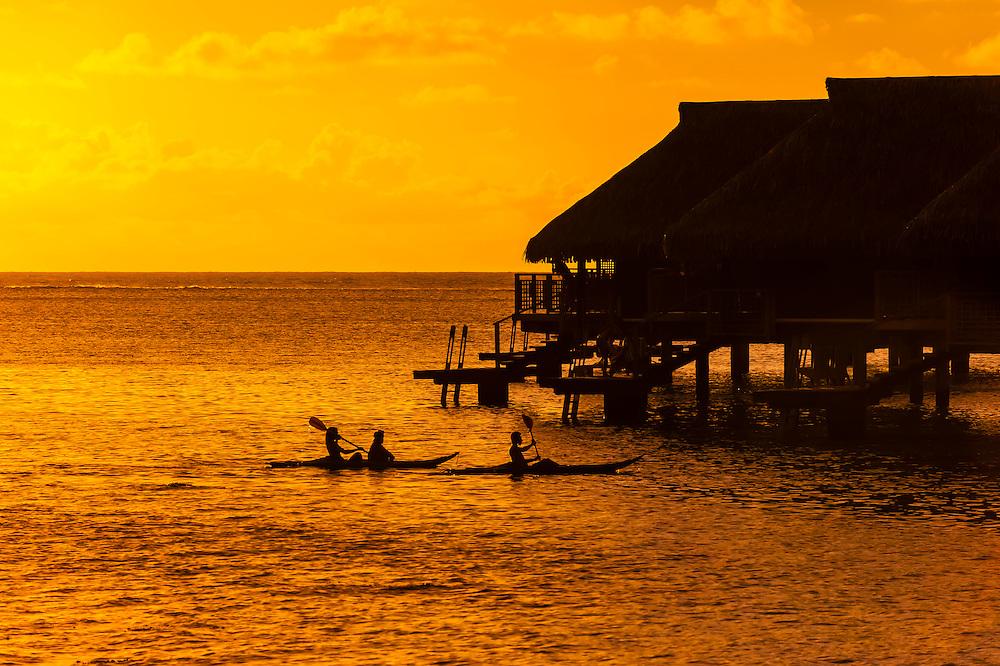 Sea kayaking in front of overwater bungalows, Hilton Moorea Lagoon Resort, island of Moorea, French Polynesia.