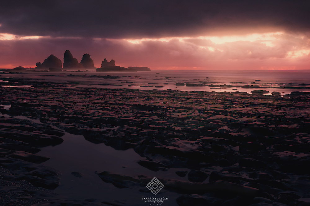 After I finished photographing several large rocks in the west coast of New Zealand and I had packaged all my gears to leave, where the clouds had closed the sky.<br /> Suddenly the light had cracked on the horizon in a majestic scene forced me to take down my gears again to photograph it.
