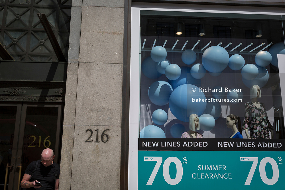 A bald'headed man checks messages next to a generic shop retailer featuring spheres in its window during 70% summer sales, on 1st August 2017, in Oxford Street, London, England.