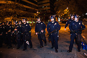 OAKLAND, CA - NOVEMBER 14, 2011: Police officers push back Occupy Oakland protesters as they begin the process of breaking down the encampment at Frank H. Ogawa Plaza. The City of Oakland cited health code violations and concerns as their reason for breaking down the encampment.
