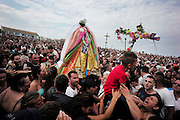"""Roma gypsies carry Saint Sara from the church of Saintes Maries de la Mer  to the sea on the 24th May<br /><br />""""Le Pelerinage des Gitans""""; the French gypsy pilgrimage of Saintes Maries de la Mer, Camargue, France<br /><br />Sainte Sara is an uncannonized saint, who legend says looked after the Christian Saints Marie Jacobe and Marie Salome, cousins of Mary Magdalene, who arrived, it is said, on the shores of the Camargue in a rudderless boat. Saint Sara is the patron saint of gypsies who come from far and wide to see her. There are even paintings of Sara as 'Kali' the black saint in Eastern Europe. Sara may have been the priestess of 'Ra' the sun-god or even servant girl to the Christian saints. No-one really knows.<br /><br />For a few weeks of the year, Roma, Gitan and Manouche gypsies come from all over Europe in May, camping in caravans around Saintes Maries de la Mer. It is a festive time where they play music, dance, party and christen their children. They all go to see Saint Sara in the crypt, kissing or touching her forehead. Many put robes on her shoulders, making her fat for the procession. In the main Gypsy procession of the 24th May, Saint Sara is allowed to leave her crypt, beneath the church, and is carried from the church to the shores of the mediterranean and back again. One day a year she is free from her prison. Hundred's of years ago the Gypsies used not even to be allowed into the church, only into the crypt like Sara...<br /><br />Roma gypsies still suffer oppressive prejudice and racism and are one of the ethnic groups the most persecuted and marginalised across Europe. The festival is one of the times where they celebrate with people of all races, their faith and traditions"""