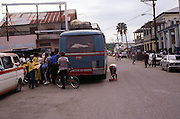 People boarding a crowded rural bus as it stops in a town, Jamaica, circa 1990