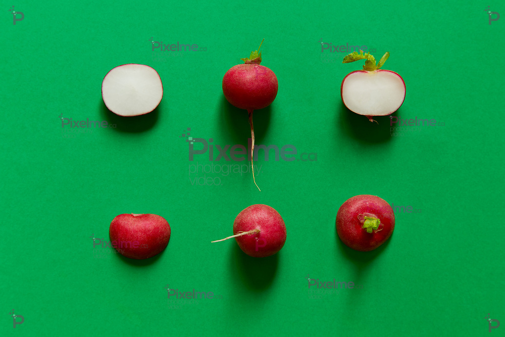 Radishes sliced viewed from above. Flat lay green background, studio.