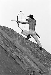 shirtless man with a bow and arrow on a cliff in California