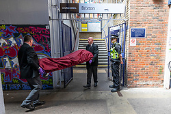 © Licensed to London News Pictures. 18/06/2018. London, UK. Coroners carry a body out of Brixton Station after three bodies were discovered near Loughborough Junction station after they were reportedly hit by a train. Photo credit: Rob Pinney/LNP